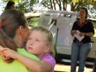 Elida, 4 anos, no colo da mãe, Noemi Gross, escutam pesquisadora da Embrapa.